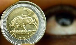A new five rand coin is displayed by a South African Reserve Bank worker during its launch at the South African Mint July 27, 2004. REUTERS/ Juda Ngwenya