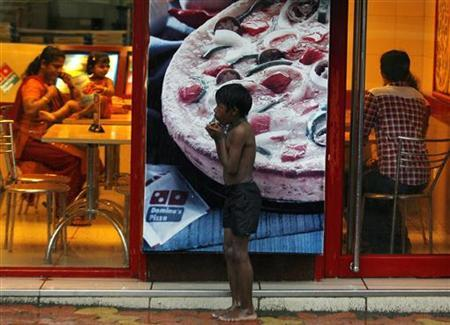 A homeless boy holds biscuits that he received as alms as he takes shelter from rain in front of a fast food shop in Mumbai November 11, 2009. REUTERS/Arko Datta/Files
