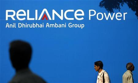 People walk pass a billboard advertising Reliance Power, at the Bombay Stock Exchange (BSE) in Mumbai February 11, 2008. REUTERS/Punit Paranjpe/Files