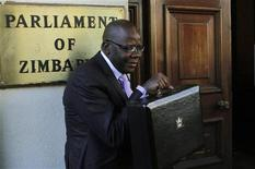Finance Minister Tendai Biti holds his Budget briefcase before delivering his mid-term budget review at Zimbabwe's Parliament building in Harare July 18, 2012. REUTERS/Philimon Bulawayo