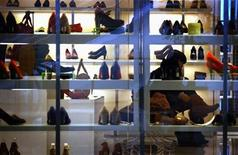 A woman tries on a pair of boots in a department store in central Beijing October 18, 2012. REUTERS/David Gray