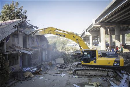 An excavator demolishes a house, owned by the Khlystov family, in the Black Sea city of Sochi September 19, 2012. REUTERS/sochinskie-novosti.ru/Artur Levedev/Handout