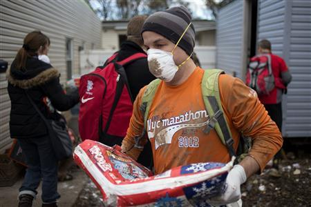 New York City Marathon runners help clear debris from the homes of a damaged neighborhood in the Staten Island borough of New York November 4, 2012. REUTERS/Adrees Latif