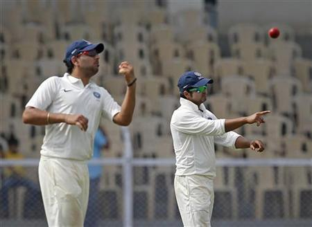 India A cricket team's Yuvraj Singh (L) throws a ball as captain Suresh Raina gestures to a player during the second day of the warm-up game against England in Mumbai October 31, 2012. REUTERS/Danish Siddiqui