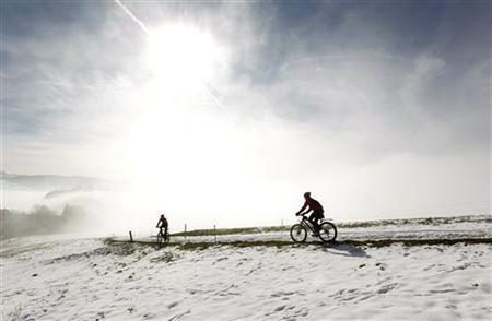 People cycle through the snow-covered landscape near the Swiss village of Hirzel south of Zurich October 31, 2012. Reuters/Arnd Wiegmann