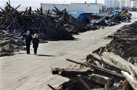 A couple walks through destroyed sections of boardwalk ripped apart by superstorm Sandy along Shore Front Parkway in the Rockaways area of the Queens borough of New York, November 4, 2012. REUTERS/Lucas Jackson