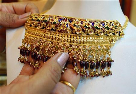 A woman touches a gold necklace at a jewellery store in Allahabad October 17, 2008. REUTERS/Jitendra Prakash/Files
