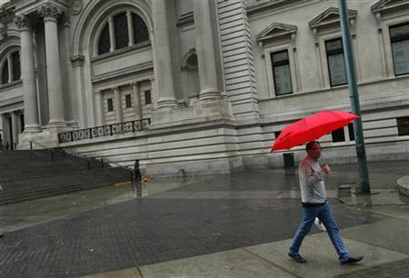 A man walks past The Metropolitan Museum of Art, which is closed, as Hurricane Sandy approaches, in New York October 29, 2012. REUTERS/Carlo Allegri