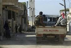 Residents look at Free Syrian Army fighters as they arrive to fight the pro-government forces, in Haram town, Idlib Governorate, October 28, 2012. REUTERS/Asmaa Waguih