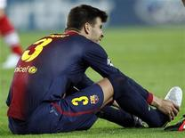 Barcelona's Gerard Pique grimances after injurein during their Champions League Group G soccer match against Spartak Moscow at Nou Camp stadium in Barcelona, September 19, 2012. REUTERS/Gustau Nacarino