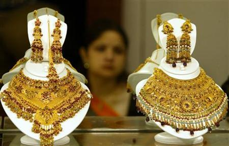A woman looks at gold necklaces at a jewellery shop in New Delhi October 10, 2005. REUTERS/Kamal Kishore/Files