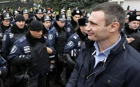 Heavyweight boxing champion and UDAR (Punch) party leader Vitaly Klitschko passes by police as they stand guard during a rally in front of Ukraine's central electoral commission in Kiev November 5, 2012.REUTERS/Anatolii Stepanov