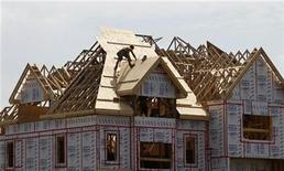 A builder works on the the roof of a new home under construction in the Montreal suburb of Brossard August 10, 2010. REUTERS/Shaun Best