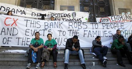 Anti-eviction activists block the entrance of a Catalunya Caixa bank headquarters during a protest in Barcelona, November 5, 2012.A group of activists had tried to re-negotiate with the bank regarding mortgages and accepting payment in kind for families that faced eviction. The sign reads, 'stop eviction'. REUTERS/Albert Gea