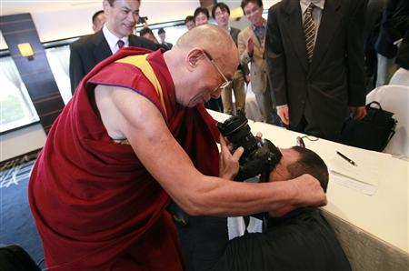 Tibetan spiritual leader the Dalai Lama (L) jokes as he pulls the ears of an photographer after a news conference in Yokohama, south of Tokyo November 5, 2012. China's leader in-waiting, Xi Jinping, will have no choice but to embark on political reforms to leave a lasting mark the way the current leadership has done with economic reforms, exiled Tibetan spiritual leader the Dalai Lama said on Monday. REUTERS/Yuriko Nakao