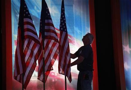 A worker adjust flags on the stage at the site of U.S. Republican presidential candidate Mitt Romney's election night rally at the Boston Convention Center in Boston November 5, 2012. REUTERS/Rick Wilking