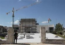 A Palestinian presidential guard watches as labourers work at the mausoleum built over the grave of late leader Yasser Arafat in the West Bank city of Ramallah July 4, 2012. REUTERS/Ammar Awad