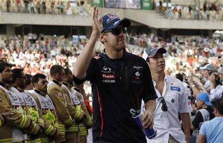 Red Bull Formula One driver Sebastian Vettel of Germany waves after the drivers' parade before the Abu Dhabi F1 Grand Prix at the Yas Marina circuit on Yas Island November 4, 2012. REUTERS/Darren Whiteside