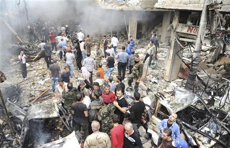 A crowd gathers in front of a building and car damaged after a bomb explosion in the Mezzeh 86 area in Damascus, in this handout photograph released by Syria's national news agency SANA, November 5, 2012. EUTERS/Sana