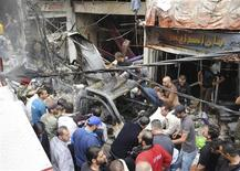 A crowd gathers in front of a building and car damaged after a bomb explosion in the Mezzeh 86 area in Damascus, in this handout photograph released by Syria's national news agency SANA, November 5, 2012. REUTERS/Sana