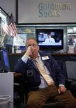 A trader looks out at the floor of the New York Stock Exchange from the Goldman Sachs both with U.S. presidential candidate Mitt Romney on the television behind him, November 5, 2012. REUTERS/Chip East (UNITED STATES - Tags: BUSINESS)
