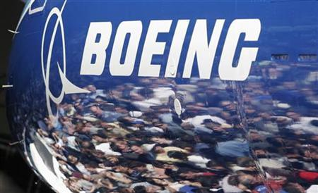Invited guests for the world premiere of the Boeing 787 Dreamliner are reflected in the fuselage of the aircraft at the 787 assembly plant in Everett, Washington, July 8, 2007. REUTERS/Robert Sorbo/Files