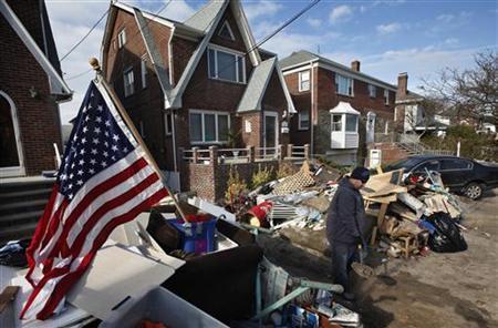Matt Long shovels sand from his house in the Rockaways neighborhood of the Queens borough of New York November 5, 2012. REUTERS/Brendan McDermid