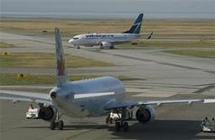 A West Jet Boeing 737-700 aircraft (top) passes an Air Canada plane while arriving at Vancouver International Airport in Richmond, British Columbia February 9, 2011. REUTERS/Andy Clark