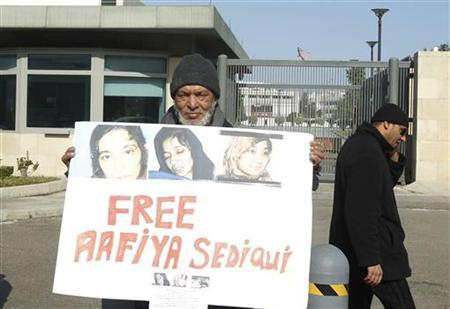 An Islamist demonstrator holds pictures of Pakistani scientist Aafia Siddiqui outside the U.S. embassy in Tunis, during a protest calling for her release February 9, 2012. REUTERS/Zoubeir Souissi /Files
