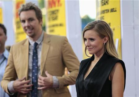 Cast member Kristen Bell poses, as her fiance and co-star Dax Shepard watches, at the premiere of ''Hit and Run'' at Regal Cinemas in Los Angeles, California August 14, 2012. REUTERS/Mario Anzuoni