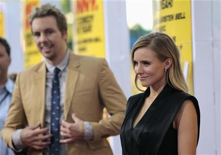 Cast member Kristen Bell poses, as her fiance and co-star Dax Shepard watches, at the premiere of ''Hit and Run'' at Regal Cinemas in Los Angeles, California August 14, 2012. REUTERS/Mario Anzuoni/Files