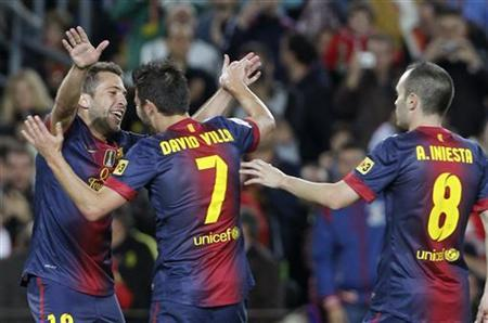 (L-R) Barcelona's Jordi Alba celebrates with team mates David Villa and Andres Iniesta after scoring a goal against Celta Vigo during their Spanish First division soccer league match at Camp Nou stadium in Barcelona November 3, 2012. REUTERS/Albert Gea