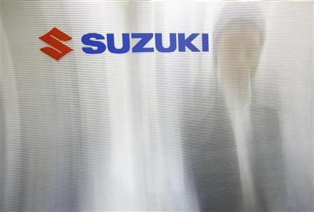 A man is seen through a compartment board with the logo of Suzuki Motor seen on it at the company's showroom in Tokyo August 2, 2012. REUTERS/Issei Kato