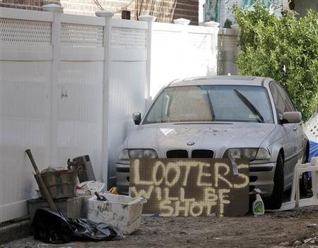 A sign reading ''Looters will be shot'' is seen next to a car on a street in the Rockaways neighborhood of the Queens borough of New York November 5, 2012. REUTERS/Brendan McDermid