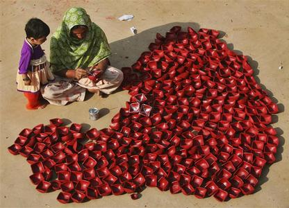 A woman paints dried clay lamps at her workplace as her daughter watches, on the outskirts of Jammu November 5, 2012. REUTERS/Mukesh Gupta