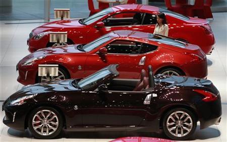 A staff passes Nissan Motor Co's vehicles displayed at company's showroom in Yokohama, south of Tokyo November 6, 2012. REUTERS/Yuriko Nakao