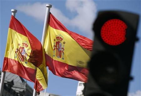 Spanish national flags flutter near a red traffic light at Cibeles Fountain in central Madrid September 24, 2012. Spain once pushed hard for Ireland and Portugal to ask for bailouts from their partners in the euro because it was keen to shelter itself from an accelerating sovereign debt crisis. Now the tables are turned and Madrid is holding back from applying for help, not least because the Spanish government knows all too well what befell its Portuguese and Irish peers once they did seek help -- voters dumped them. REUTERS/Sergio Perez (SPAIN - Tags: BUSINESS POLITICS)