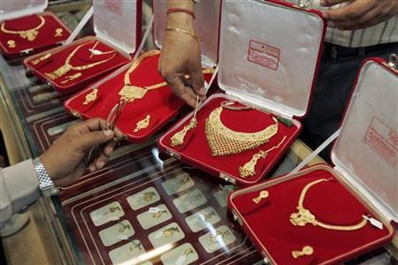 A shopkeeper shows gold jewellery to a customer inside his shop in New Delhi June 12, 2008. REUTERS/Danish Ismail/Files