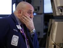 Un trader osserva le quotazioni dei titoli sugli schermi durante una seduta di borsa. REUTERS/Chip East