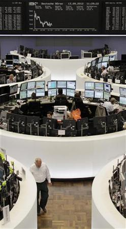 Traders are pictured at their desks in front of the DAX board at the Frankfurt stock exchange September 13, 2012. REUTERS/Remote/Amanda Andersen (GERMANY - Tags: BUSINESS)