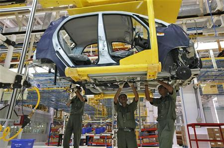 Employees work inside a plant for the Tata Nano car at Sanand in Gujarat June 2, 2010. REUTERS/Amit Dave/Files