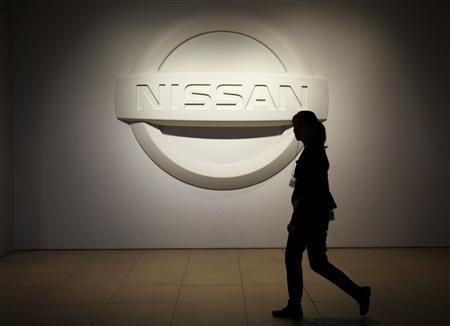 A woman walks past a logo of Nissan Motor Co. at the company's showroom in Yokohama, south of Tokyo November 6, 2012. REUTERS/Yuriko Nakao