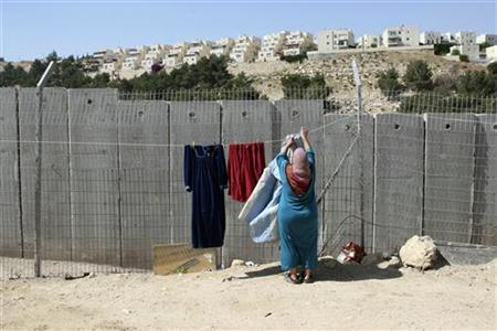 A Palestinian woman hangs laundry outside her house in front of a section of the controversial Israeli barrier in the Shuafat refugee camp in the West Bank near Jerusalem May 4, 2010. REUTERS/Ammar Awad
