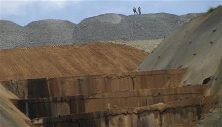 Workers stand at the top of a mountain of waste rock at Newmont Mining Corp's copper and gold mine on Indonesia's Sumbawa island September 21, 2012. REUTERS/Neil Chatterjee