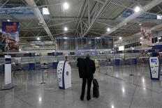A passenger looks at an announcement board inside the Athens Eleftherios Venizelos airport a few hours before a work stoppage by flight controllers begins in Athens November 6, 2012. Greek workers begin a 48-hour strike on Tuesday to protest against a new round of austerity cuts that unions say will devastate the poor and drive a failing economy to collapse. REUTERS/John Kolesidis