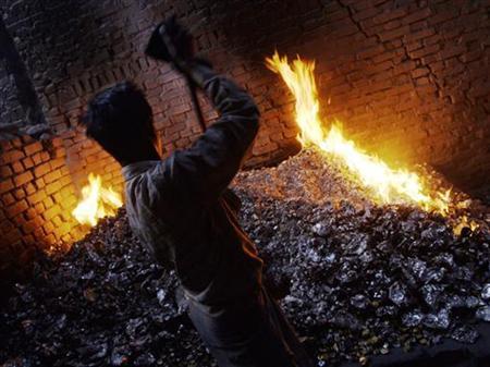 A worker melts waste bottle caps to get aluminium inside a workshop in Mumbai December 12, 2005. REUTERS/Adeel Halim/Files