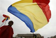 People wave flags during a rally in front of Victoria palace, Romania's government headquarters, in Bucharest October 21, 2012. REUTERS/Bogdan Cristel