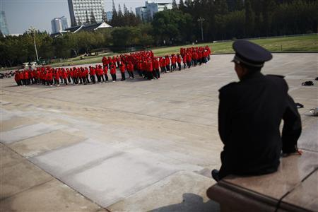 A security guard watches as Fudan University's student members of the Chinese Communist Party stand in formation to create the party's emblem, a hammer and sickle, to mark the 18th National Congress of the Communist Party of China (CPC) which kicks off this Thursday, in Shanghai November 6, 2012. Close to 260 students participated in the display. REUTER/Aly Song