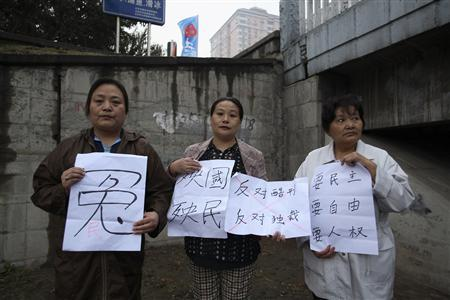 Mao Hengfeng (C) holds signs bearing slogans as she protests with Jin Yuehua (L) and Shen Peilan in Beijing September 26, 2009. REUTERS/Handout/Amnesty International
