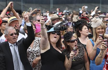 Race goers cheer the winning horse Green Moon after it won the Melbourne Cup at Flemington Racecourse in Melbourne November 6, 2012. Green Moon thundered down the straight to win the Melbourne Cup on Tuesday, upsetting a host of highly fancied foreign horses to bring Australia's most coveted racing prize back home. REUTERS/Brandon Malone